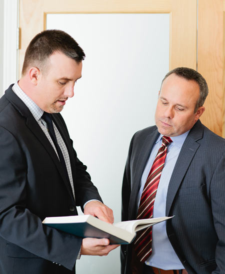 Attorneys Rob Hamilton and Luke Antonsen reviewing a law book